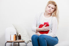 Woman feeling stomach cramps sitting on cofa Royalty Free Stock Photography