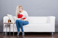 Woman feeling stomach cramps sitting on cofa Royalty Free Stock Photos
