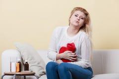 Woman feeling stomach cramps sitting on cofa Stock Photo