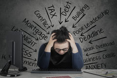 Woman feeling stressed with financial chart on desk. Businesswoman feeling stressed with financial chart on the desk while holding her head royalty free stock photography