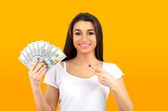 Woman feeling super happy holding fan of dollar money. Portrait of a rich woman feeling super happy holding fan of dollar money isolated on yellow background stock photography