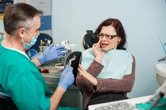 Woman feeling toothache, touching cheek with hand at dental clinic. Senior dentist trying to help with dental tool Stock Photo