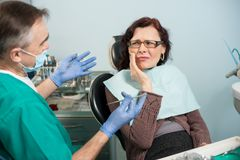 Woman feeling toothache, touching cheek with hand at dental clinic. Senior dentist trying to help Royalty Free Stock Photography