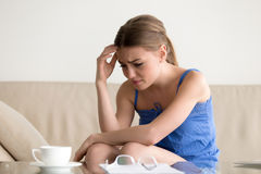 Woman feeling upset because of loan debt letter. Stressed confused young woman feeling frustrated after reading paper letter, written bank notification. Credit royalty free stock images