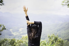 Woman feeling victorious facing on the mountain, Royalty Free Stock Image