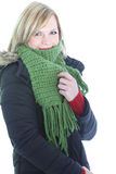 Woman feeling the winter cold. Snuggling down into her warm knitted scarf and overcoat isolated on white Stock Photo