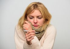 Woman feels badly ill sneezing. Girl in scarf hold thermometer and tissue close up. Measure temperature. High stock photography