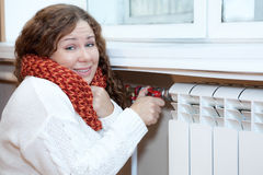 Woman feels cold when turning thermostat of central heating con. Young woman feels cold when turning thermostat of central heating con Stock Photography