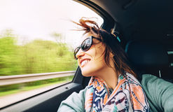 Woman feels free and looks out from open window car Stock Photos
