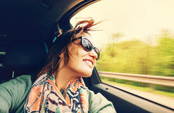 Woman feels free and looks out from open window car stock image
