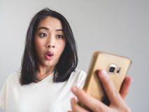 Woman feels surpriesed on her smartphone display. royalty free stock image