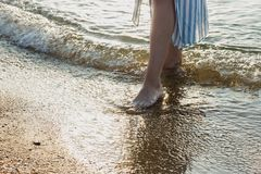 Woman feet in barefoot touched by gentle sea surf waves on sand beach. Woman feet in barefoot stand still and touched by gentle sea surf waves on golden sand Royalty Free Stock Images