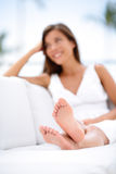 Woman feet - barefoot woman relaxing in sofa stock photography