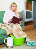 Woman with feet in basin Stock Images