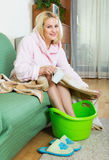 Woman with feet in basin Stock Photos