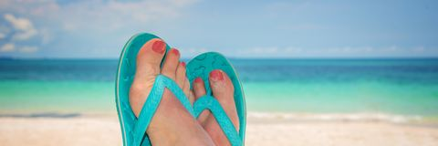 Woman feet with blue flip flops, beach  in the background Stock Photo