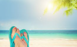 Woman feet with blue flip flops, beach and sea in the background, summer concept stock photo