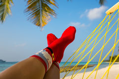 Woman feet with christmas sock in hammock on the beach Stock Photos