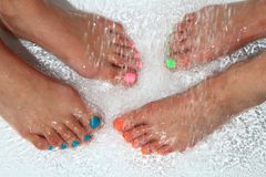 Woman feet with color nails in water Stock Images
