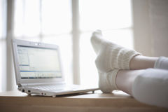 Woman With Feet On Desk Near Laptop Royalty Free Stock Photography