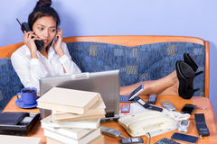 Woman with feet on desk. Young woman with feet on desk phone with both hands Royalty Free Stock Photos
