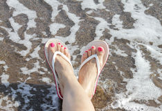 Woman Feet with flip flops on the Beach. Beautiful woman with pedicured toes and flip flops laying on the mediterranean beach royalty free stock photography