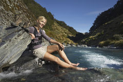 Woman With Feet In Forest River. Side view of a young woman dipping her feet in forest river Royalty Free Stock Photo