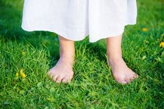 Woman feet on the grass with white cloth. Woman feet on the grass with white cloth Royalty Free Stock Photo