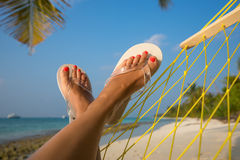 Woman feet in hammock on the beach Stock Images
