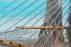 Woman feet in hammock on the beach, blue sea background, Aitutaki stock photography