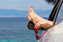 Woman feet and hand holding sunglasses out of car window stock photography