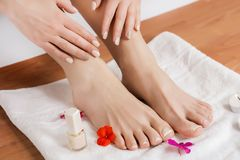 Woman feet and hands with nails manicure and pedicure on white towel with flowers in beauty salon royalty free stock photography