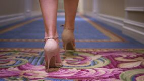 Woman feet in high heeled shoes walking on carpet floor back view