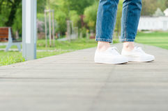 Woman feet with jeans and white casual shoes in closeup. Walking in the park Stock Image