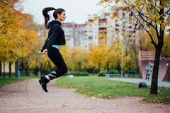 Woman feet jumping, using skipping rope in park. Royalty Free Stock Image