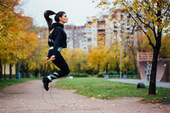 Woman feet jumping, using skipping rope in park. Royalty Free Stock Images
