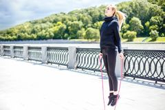 Woman feet jumping, using skipping rope in park. Beautiful sports girl doing cardio exercises royalty free stock images