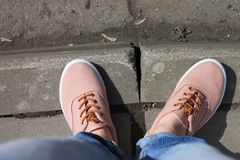 Woman feet in orange sneakers standing on a pavement near the asphalt road stock image