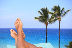 Woman feet overlooking a tropical ocean. Bare female feet resting on a recliner overlooking a blue tropical ocean with palm trees conceptual of a summer vacation Royalty Free Stock Photos