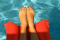 Woman feet in the pool Stock Photography