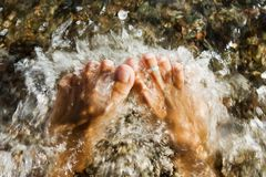 Woman feet pounded by wavs Stock Photo