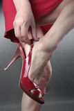 Woman feet putting on red heel shoes Stock Photography