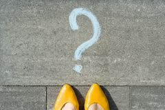Woman feet with question mark in front of her legs painted on the asphalt. Woman feet with question mark in front of her legs painted on the asphalt stock photo