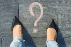 Woman feet with question mark in front of her legs painted on the asphalt.  Stock Images