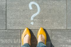 Woman feet with question mark in front of her legs painted on the asphalt.  royalty free stock image