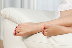 Woman feet with red pedicure on a couch Stock Image