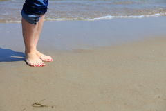 Woman feet with red pedicure relaxing on sand Stock Photos