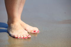 Woman feet with red pedicure relaxing on sand Royalty Free Stock Images