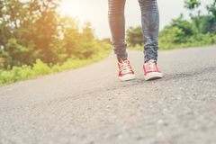 Woman feet with red sneaker shoes walking on the roadside. Woman feet with red sneaker shoes walking on the roadside background royalty free stock photography