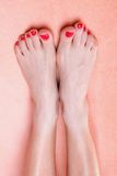 Woman feet with red toenails on towel Royalty Free Stock Photo
